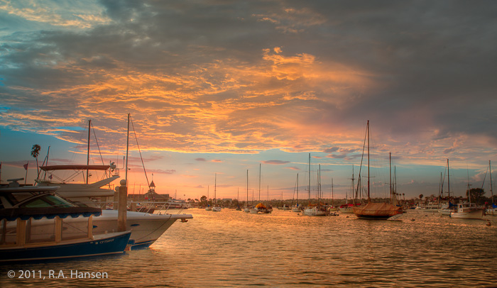 Boats rest at anchor as the water reflects the colors of dramatic sunset-lit clouds above