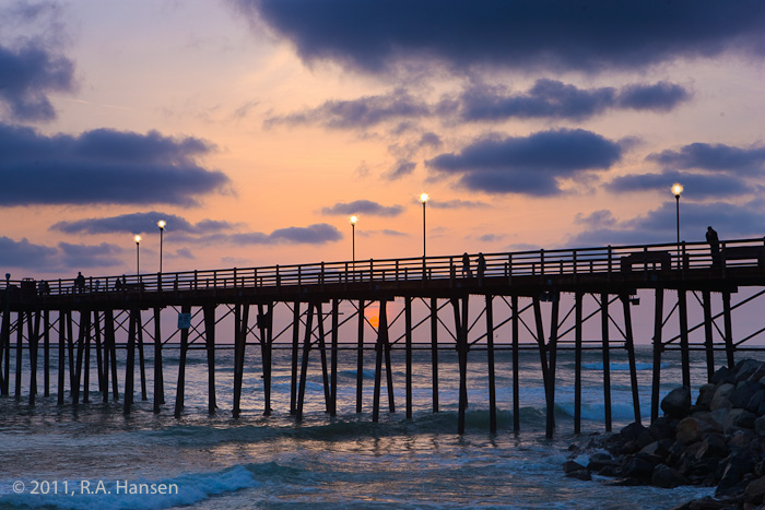 A few hardy pedestrians stoll along the pier as the sun sets behind the clouds