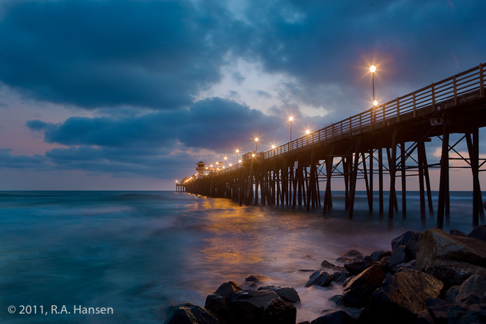 The sun has set under a cloudy sky and the pier lights have come on, glowing with their reflection in the water below
