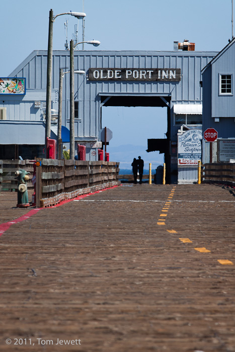 A couple stroll leisurely beneath the archway of this historic seafood restaurant and fish market at the end of Port San Luis...