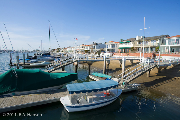 Boats rest at anchor at docks for each homeowner along this shoreline