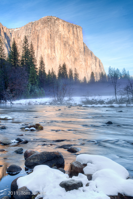 Snow-covered rocks provide the foreground for this winter view of El Capitan reflected in the Merced River. Photo by Tom Jewett...