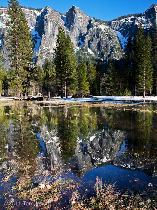 On a winter morning, a pool formed by the Merced River provides an almost mirror-like image of the snow-capped peaks. Photo by...