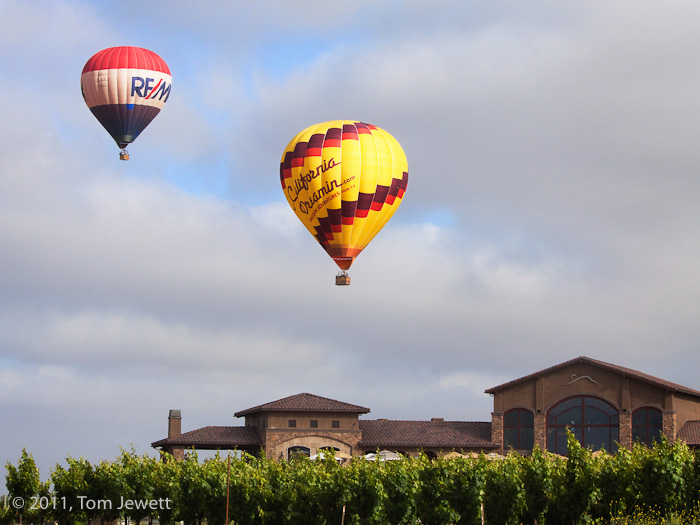 At the annual Temecula festival, two colorful balloons soar effortlessly over the vineyards and headquarters of a local winery...