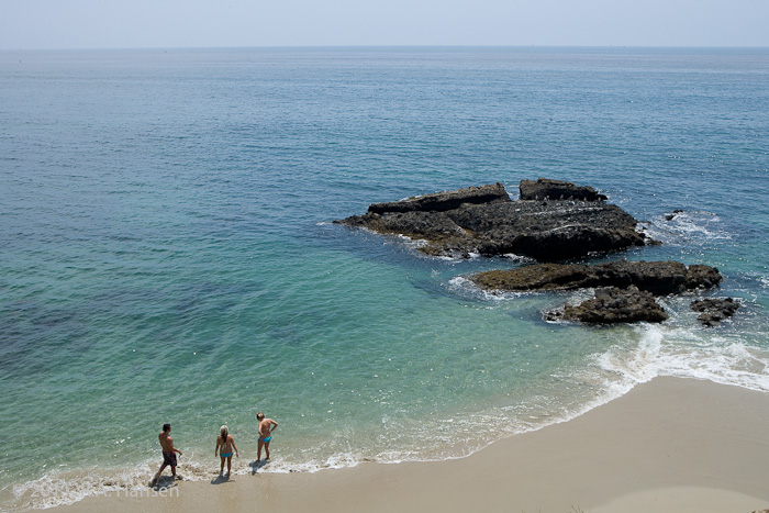 Three bathers explore the surf and rocks along the coastline