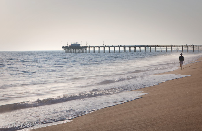 A lone walker strolls along the beach and surf, with the iconic pier in the background
