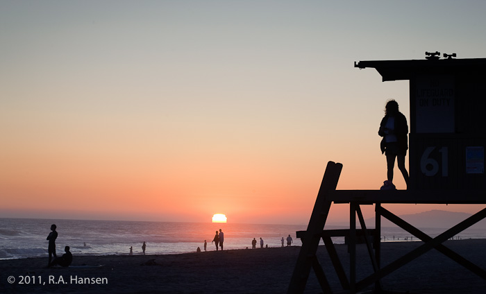 Sunset over the beach with a lifeguard station in the foreground and the Palos Verdes Peninsula in the background.