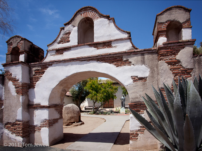 Entrance archway. The stucco has obviously been repaired, with the original brickwork showing through. In the background is a...