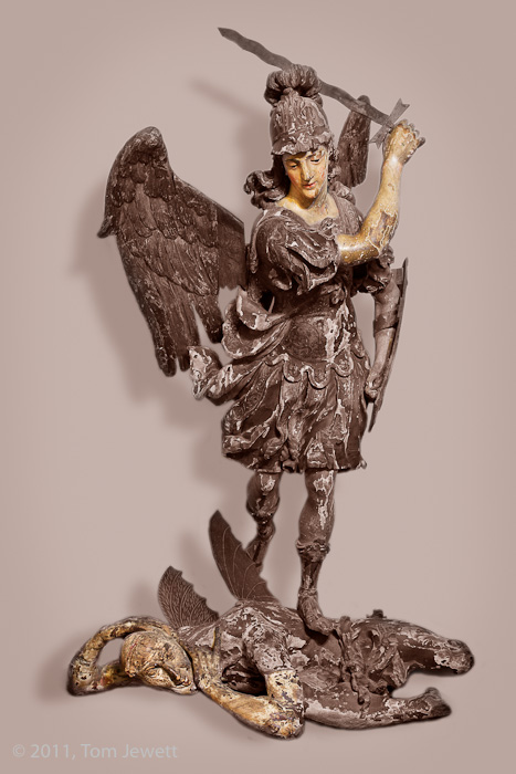 Life-size wood carving of the Archangel St. Michael slaying the Devil, allegorically representing the victory of good over evil...